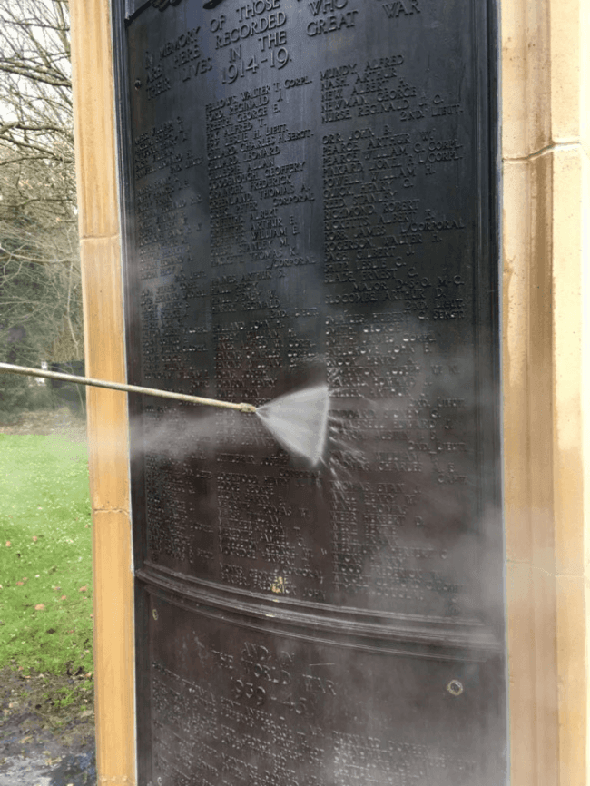 steam cleaning a bronze war memorial