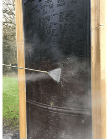 steam cleaning a bronze war memorial